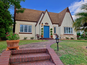 The blue door pops and the topiaries on both sides of the door create a focal point. The home is an English tundra build in 1925. There is a brick sidewalk that leads to the front door.
