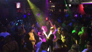 Also, Enigma Dance Bar prepares for Drag Show People are facing the stage in the picture with colorful dance lights.