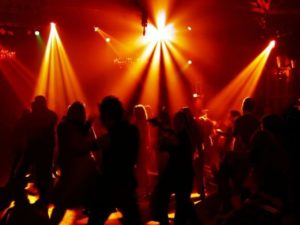 Furthermore, Orange disco lights fill the dance floor and all you can see are shadows of dancers having a blast.