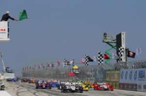 Although the track has many curves, as you can see there is great speed by the cars.  In the picture are race cares and white and black checkered flags.