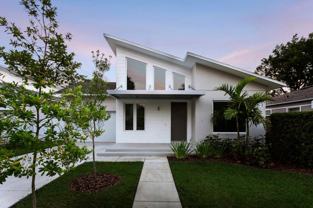 Moreover, notice the large windows imbedded in the Mid Century steep vaulted ceilings. And the outside color is white with gray trim. Furthermore, the porch roof is a modern metal flat roof.
