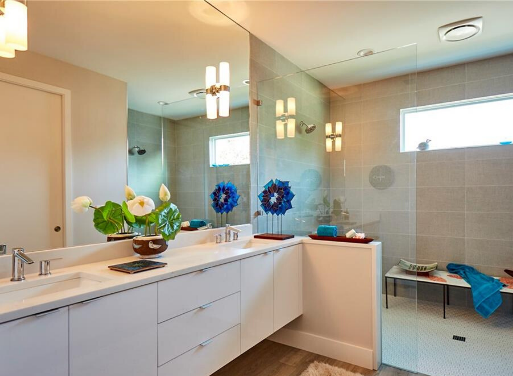 First,The large horizontal window gives blue sky views from the shower. And the full wall vanity mirror reflects the light throughout the bathroom.