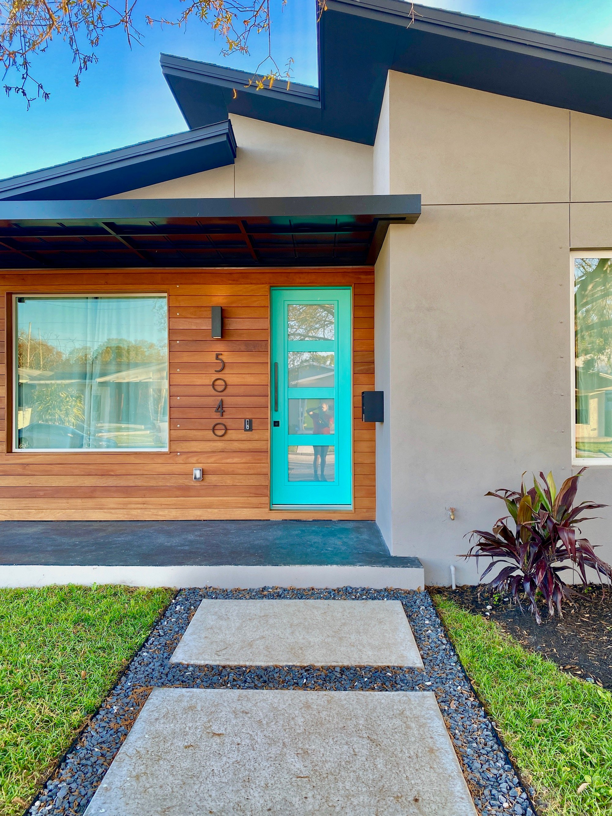 Therefore, A custom Modern Sidewalk and a stained concrete front porch welcome guests. Also, the front door is a tiffany blue color.