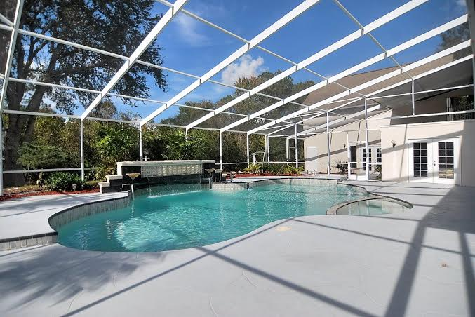 Beautiful screened pool with hot tub and waterfall