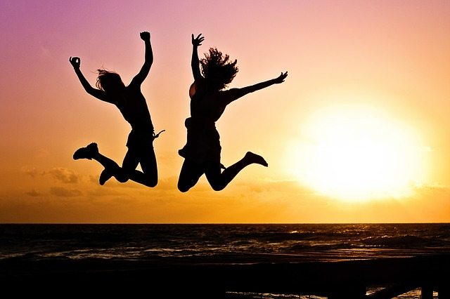 two people jumping on a beach