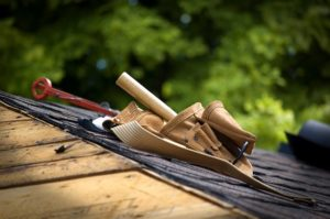 roofer's tool belt on top of a house