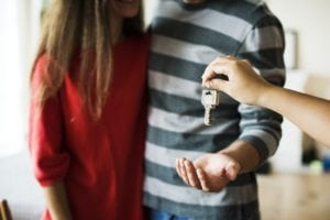 Young couple being handed the keys to their new home.