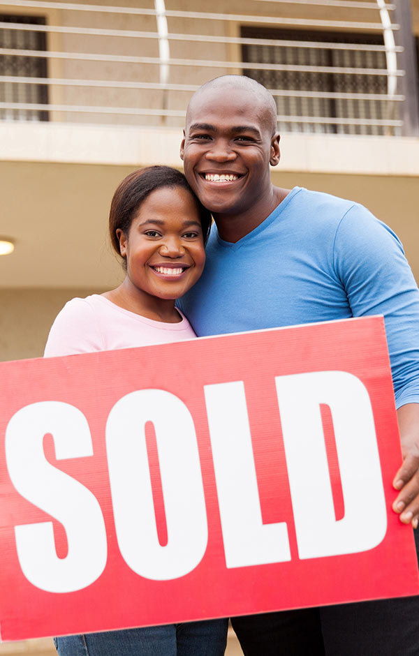 happy couple who just sold home in front of house