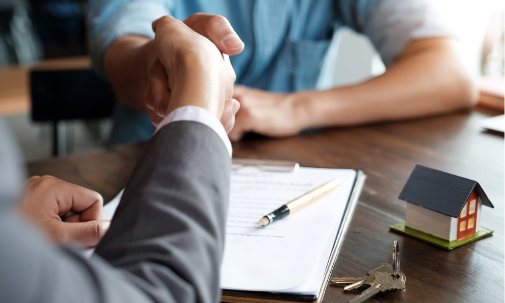 Two people shaking hands on a residential real estate deal with keys and a contract on the agent's desk