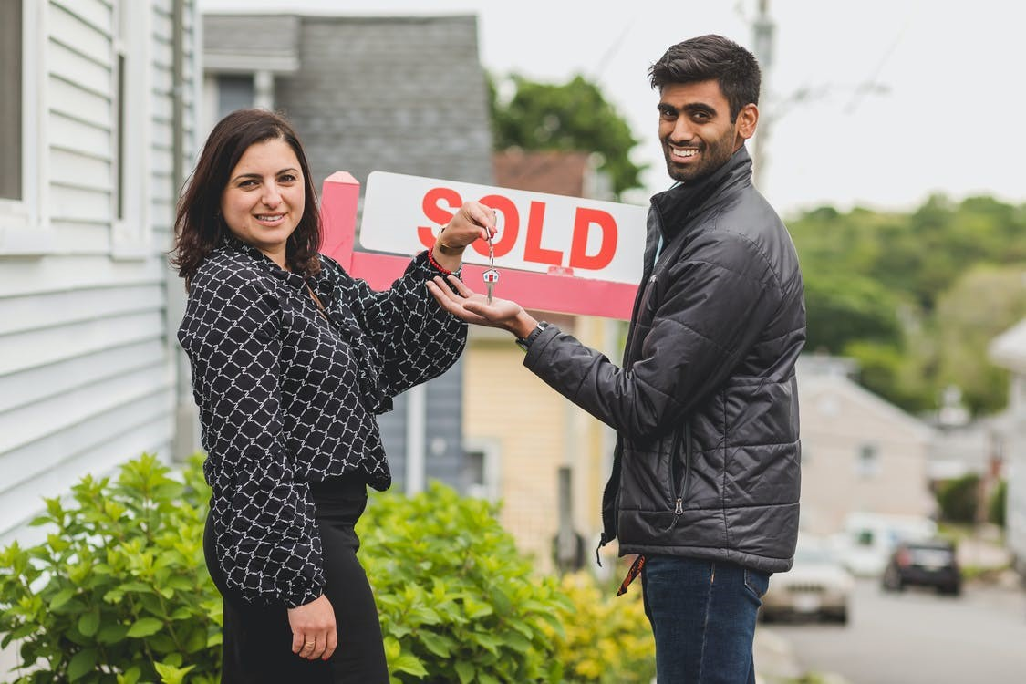 real estate agent giving a house key to the buyer