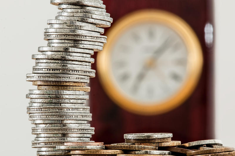 stacked coins with clock in background