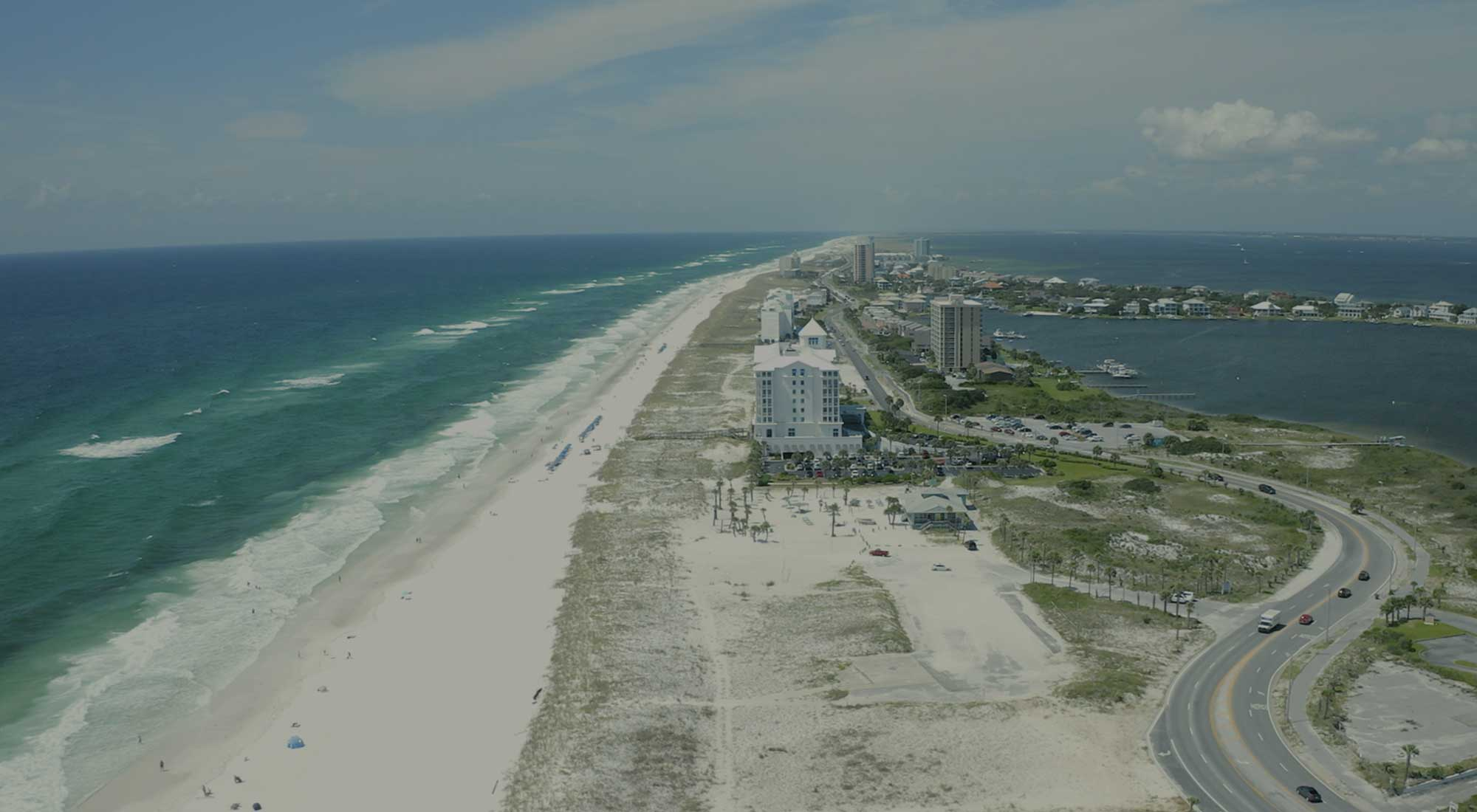 drone view of blue-green water, white sands and Pensacola Beach condos