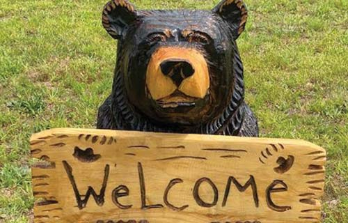 bear holding welcome sign
