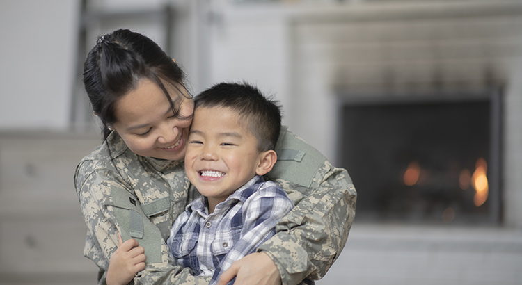 Service member hugging her child