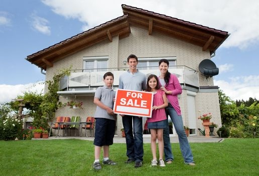 a family holding a 'for sale' sign