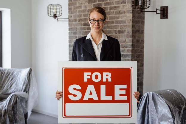 A woman holding a for sale sign