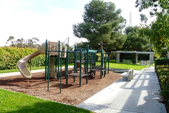 The community park with a tot lot is next to the pool and spa
