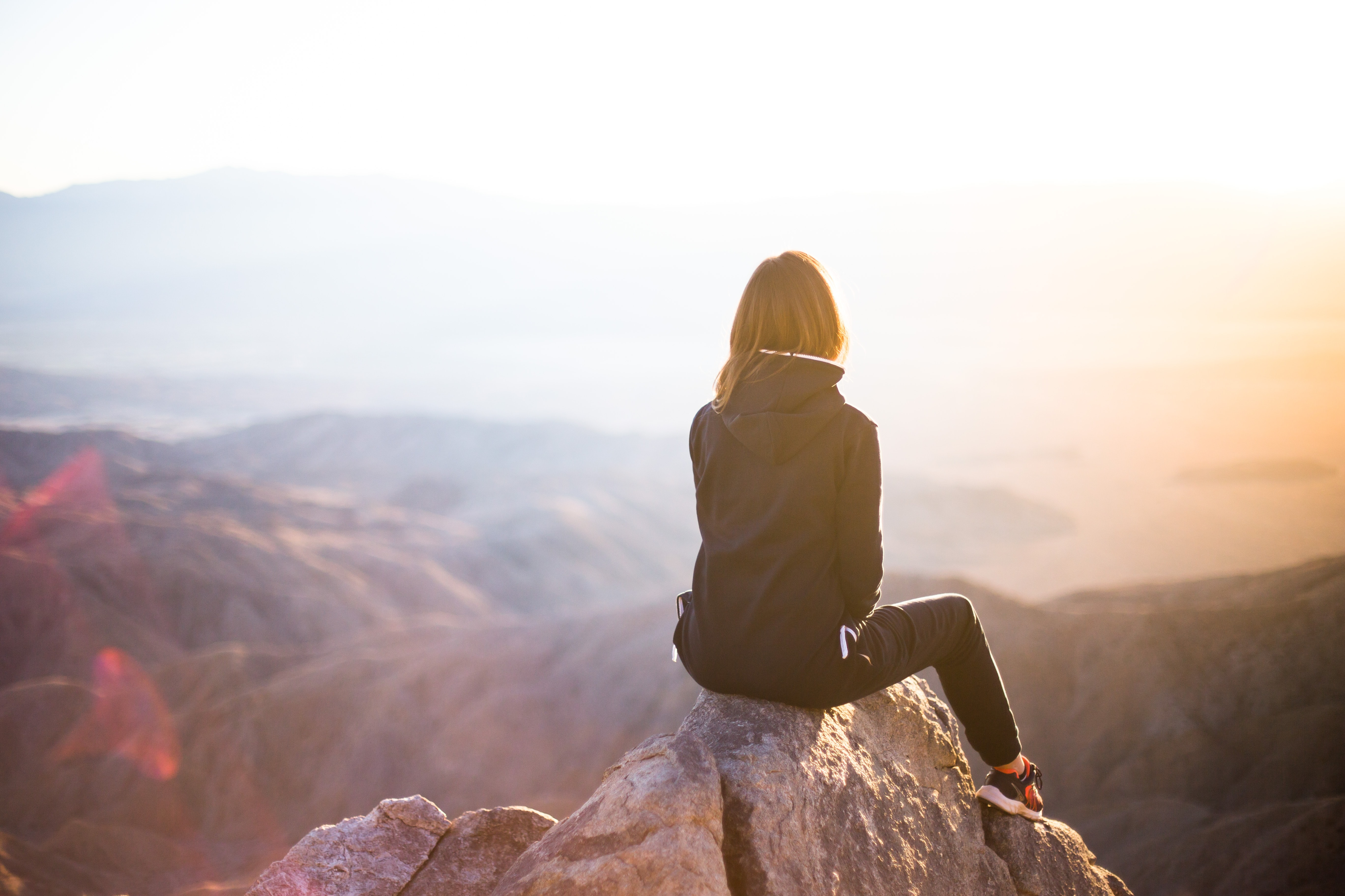 A woman sitting on a mountain top looking at the sunset