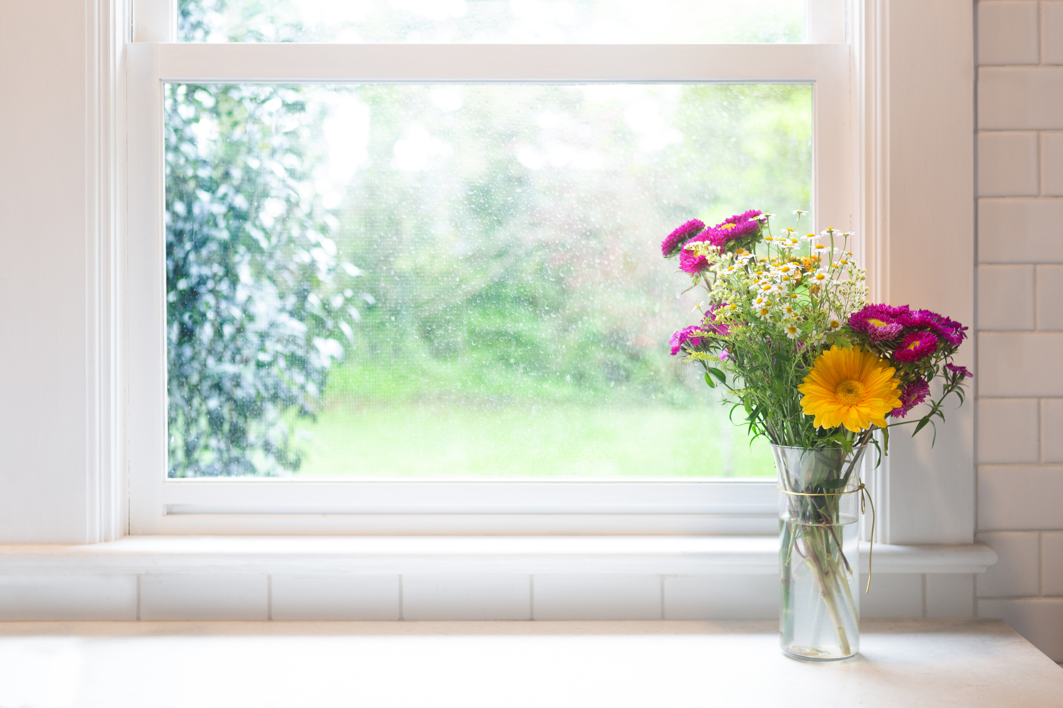Is Poulsbo WA a Nice Place to Live? Image of a boquet of flowers sitting in front of a window on a summer day.