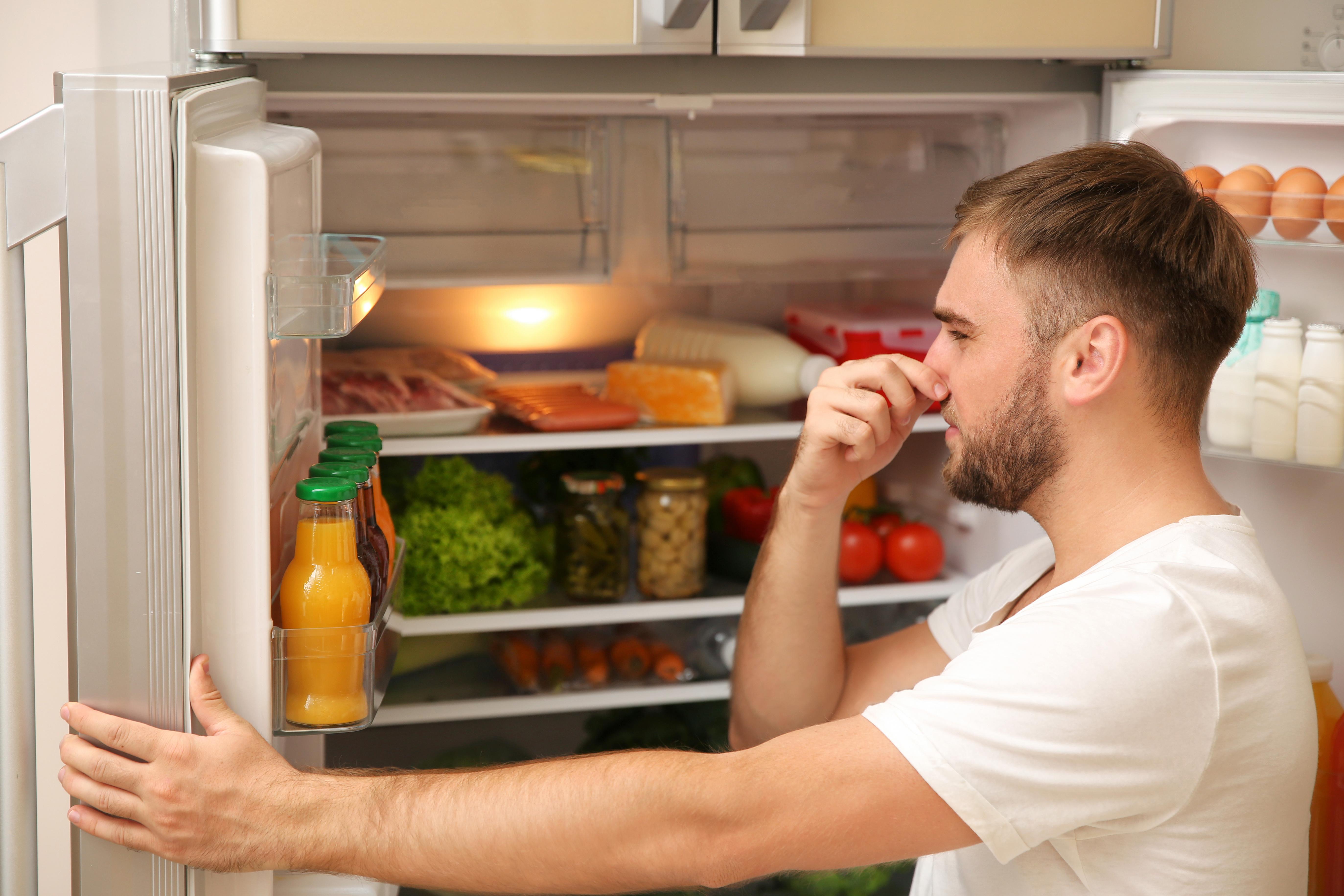 man cleaning stinky fridge