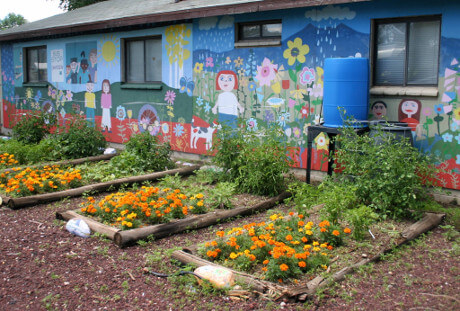 Sunnyside building mural and flower beds.