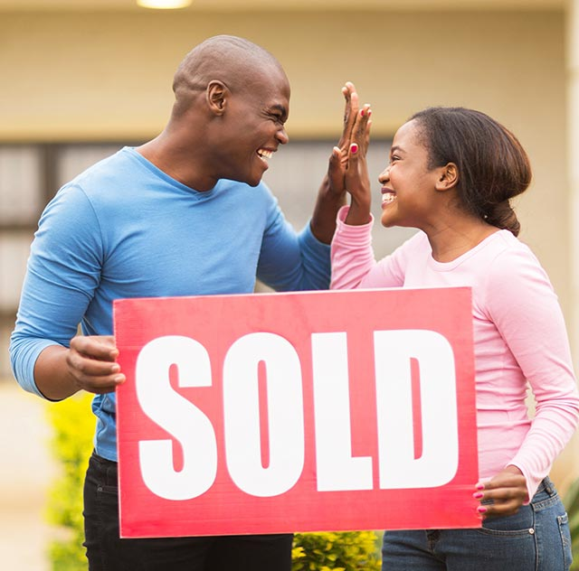 couple holding sold sign outside home in yuma az