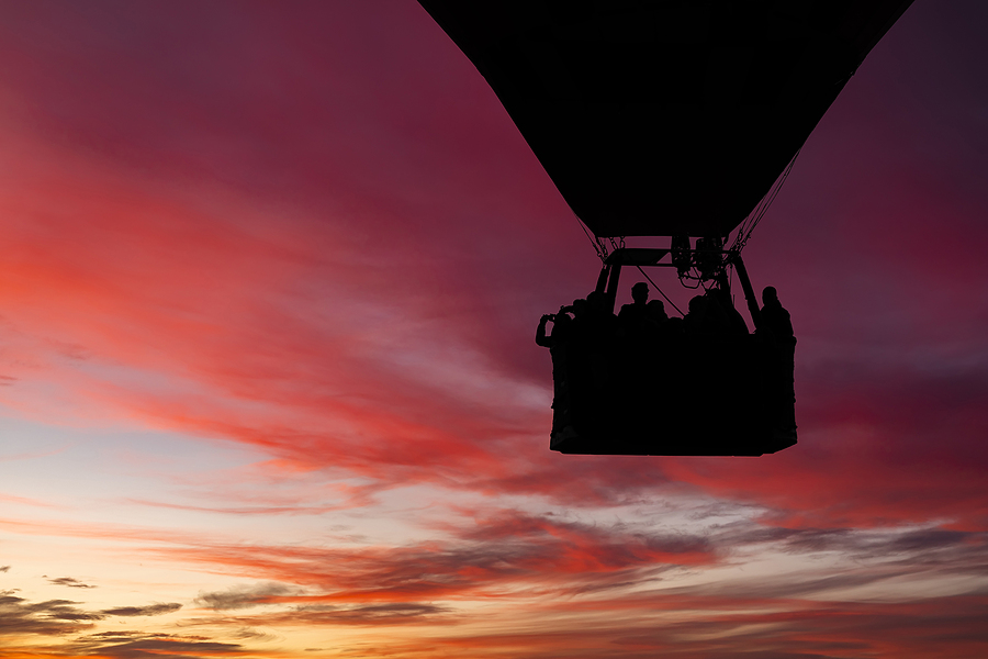 People from Oak Creek Canyon homes ride a hot air balloon.