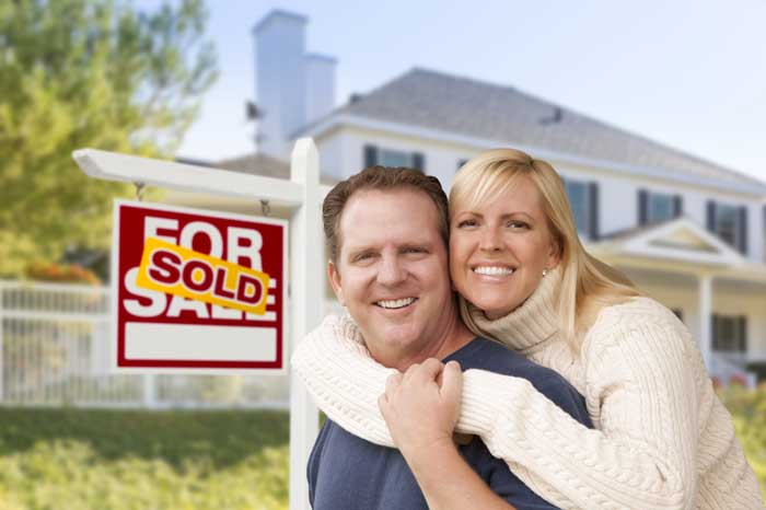 Happy couple with sold sign in front of house