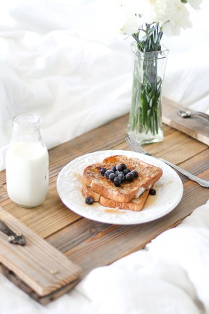 french toast, milk and flowers on serving tray