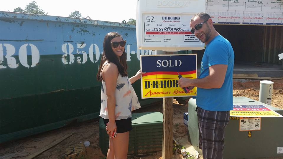 couple putting up a Sold sign