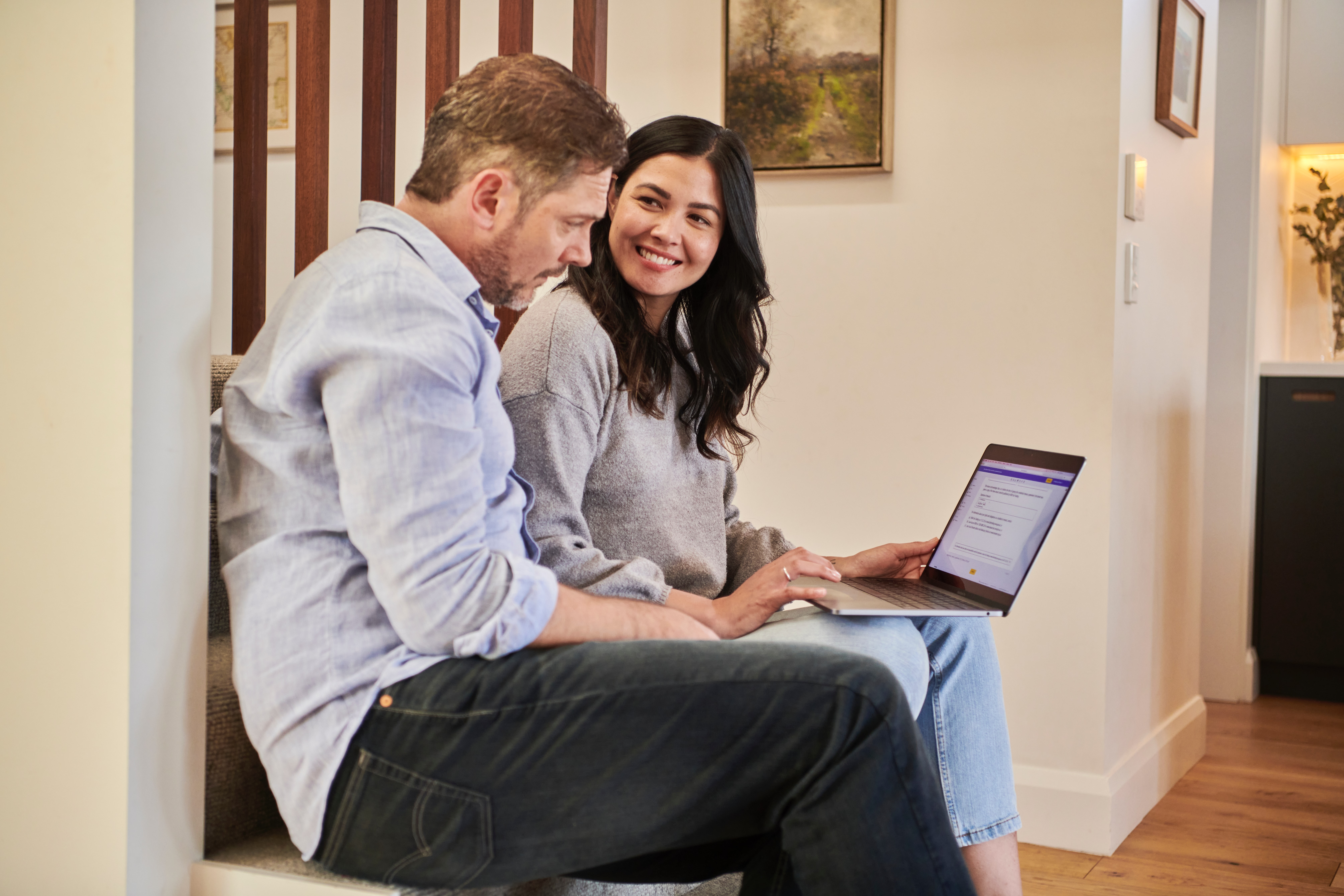 A woman sitting in the stairs next to a man showing him something on a laptop