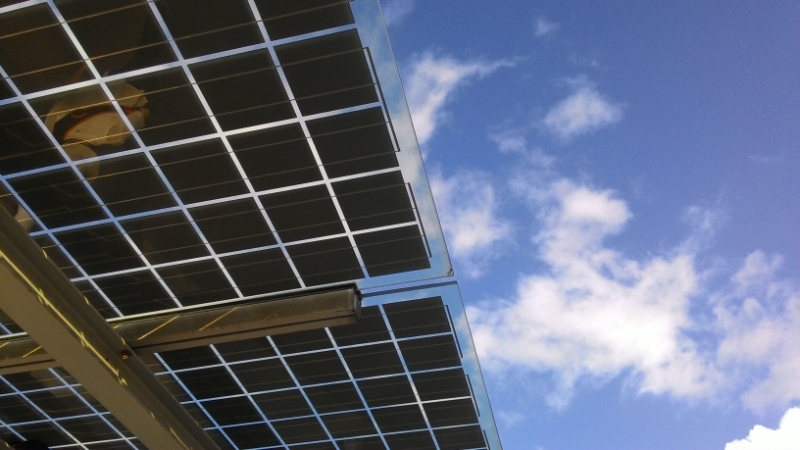 solar panels against a blue sky with clouds