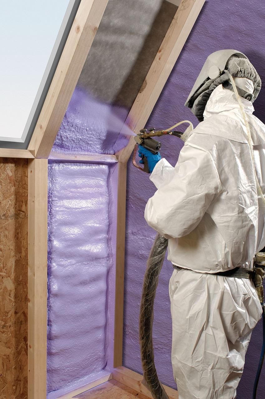 person in full protective gear sprays foam insulation in attic