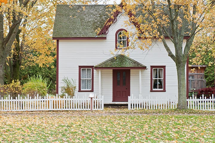 white house with white picket fence and trees surrounding it, all the leaves are yellow and falling to the ground