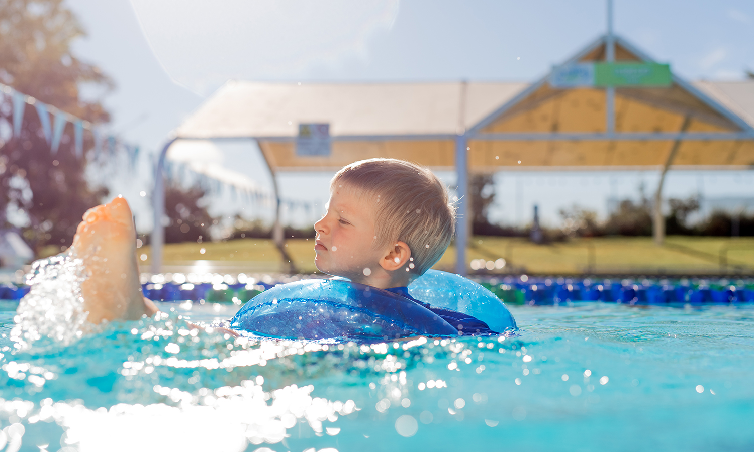cute boy swimming in the pool with a float