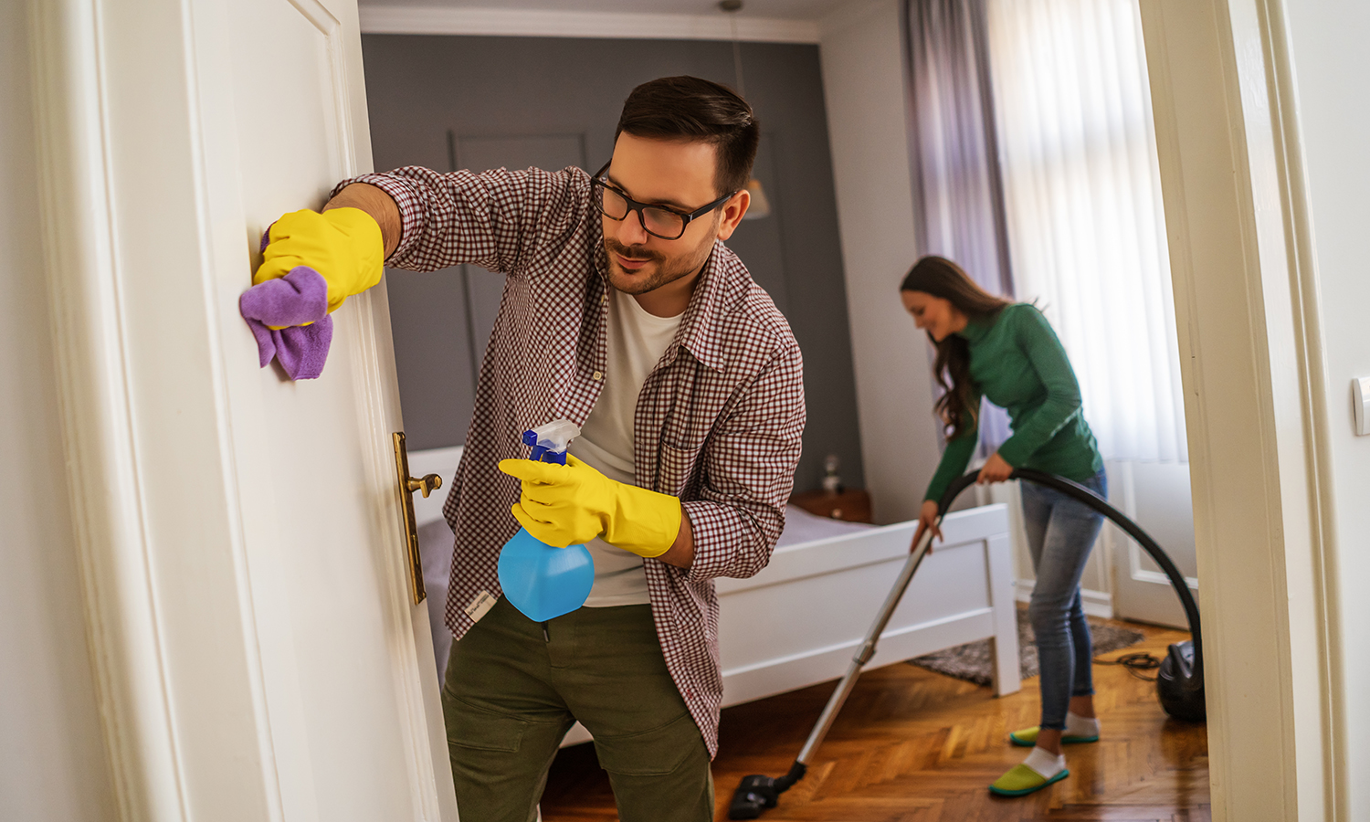 couple cleaning their house to prepare for selling it