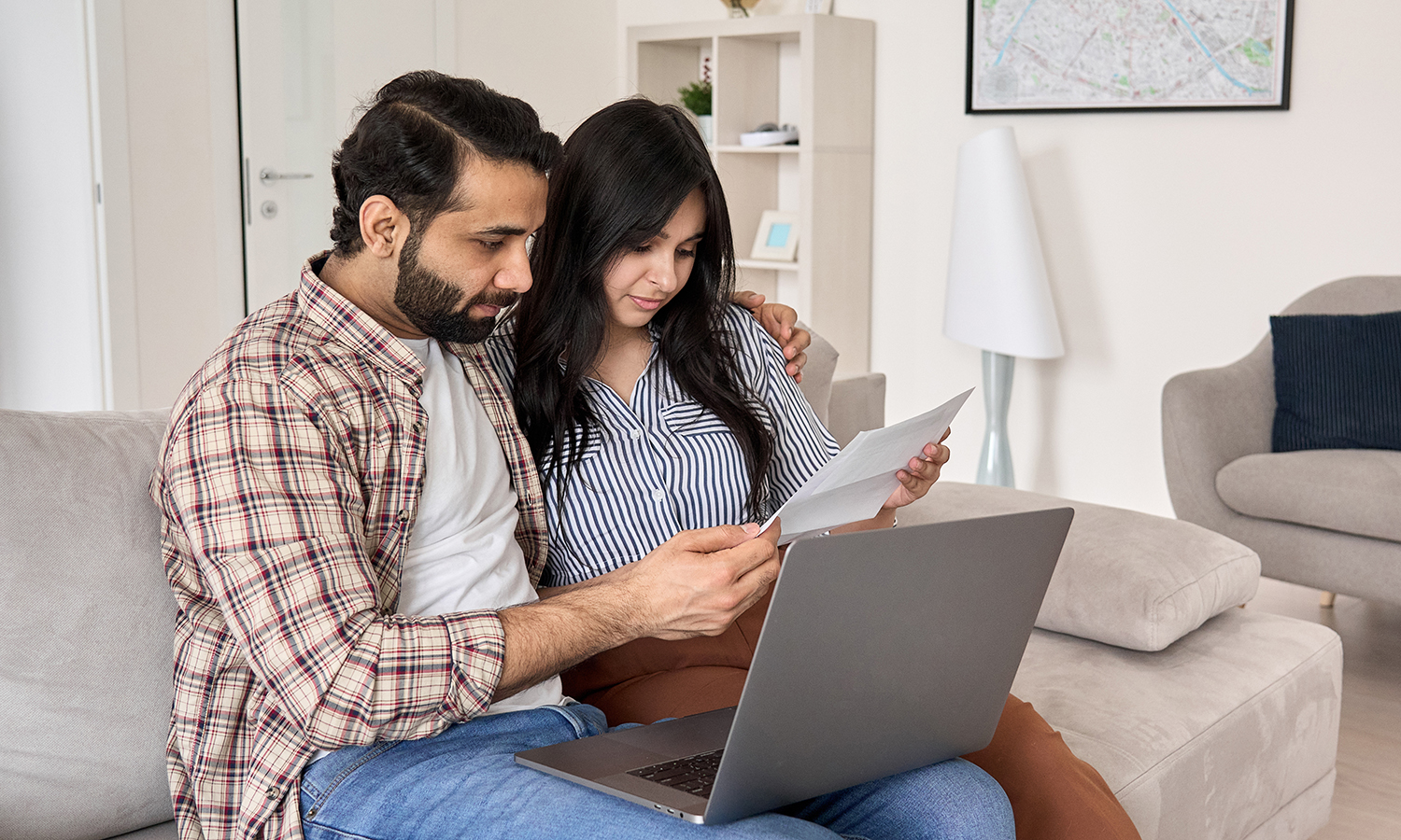 young couple looking at their 401k on a laptop