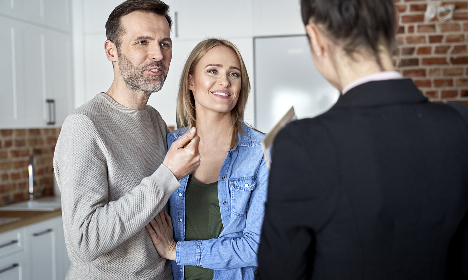 couple asking a realtor if they should sell their house as is or fix it up