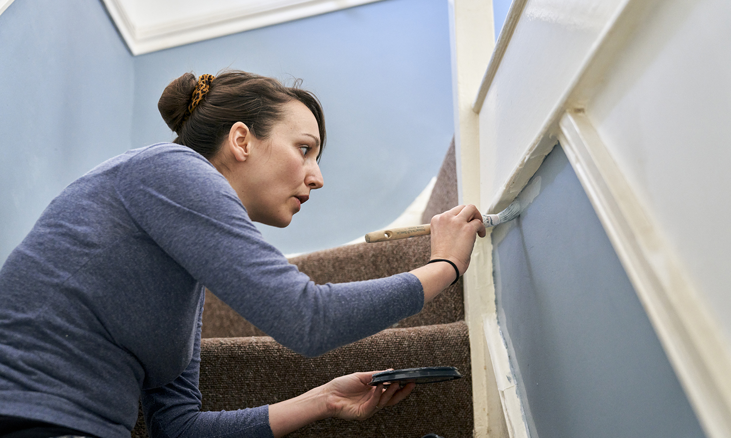woman fixing up her home by painting a staircase