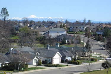 Street scene of Gold Hills subdivision, Redding CA with homes & mountains