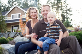 family sitting in front of suburban house