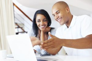 Smiling couple looking at a computer researching their budget.