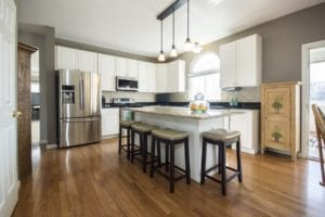 Large kitchen interior with hardwood floors, sleek chrome appliances, and a large island with bar seating.