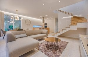 Luxurious living room with winding staircase, bright furniture, and hanging light fixtures.