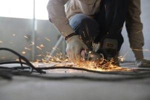 Man using a power-saw to cut through a floor.