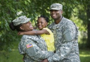 Two parents in military fatigues smiling as they hug their child.