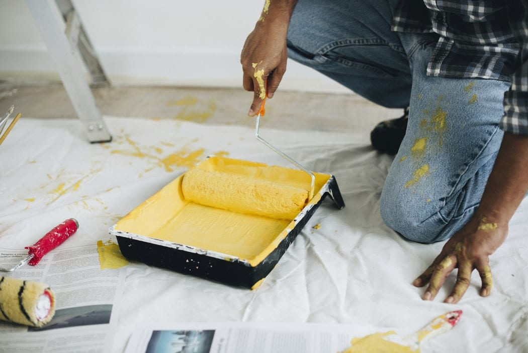 A man rolling a paint roller in a tin of yellow paint.