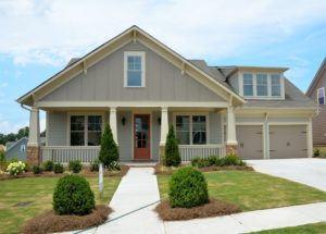 A single-level ranch-style house with a front porch, two-car garage, and well-maintained front yard.