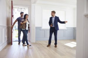 Couple walking through a home with a Realtor there to show them around.