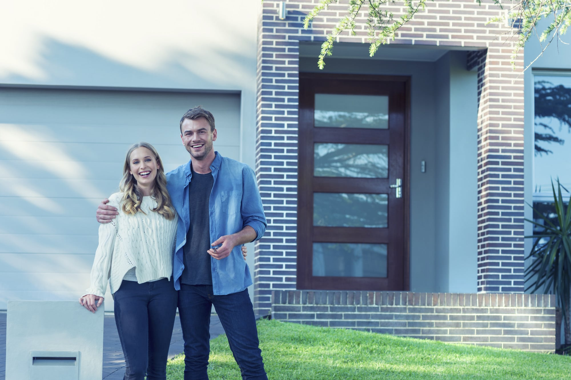 A young millennial couple standing in front of the home they've just purchased.
